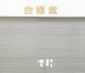 地震の影響で閉鎖されてしまった金龍堂まるぶん店。シャッターにはお客様からの応援の声が貼られている。